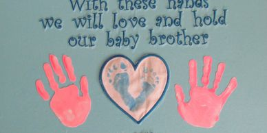 Sibling prints added to newborn's foot prints.