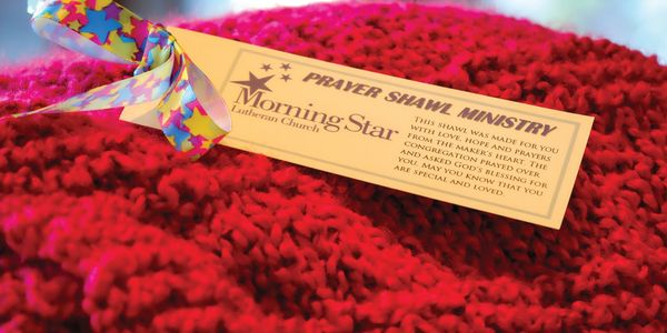 Red knitted shawl with a prayer shawl ministry ministry tag.