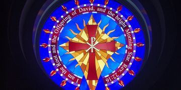 The chapel's stain-glass window depicting a cross and the bible verse from Revelations 22:16.