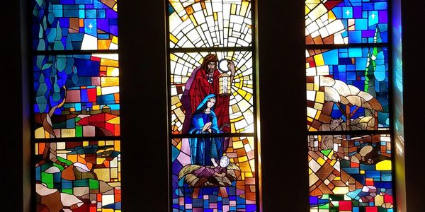 three sesctions of stained glass depicting the birth of Jesus.