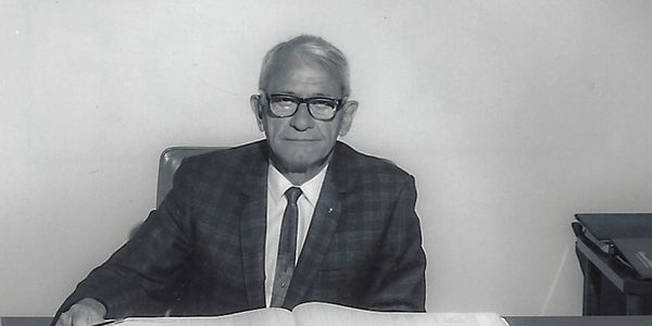 Older man with glasses in front of a ledger book