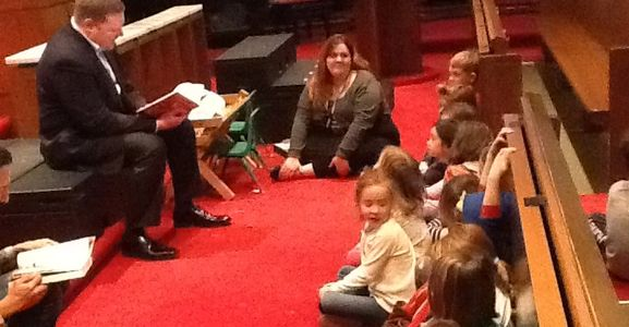 Pastor Chris reading to a group of pre-schoolers and their teachers.