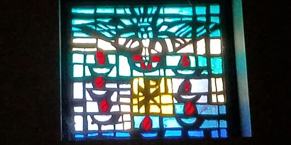 Stained-glass symbols or confirmation including a dove and candles.