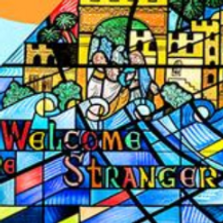 "Stained-glass which says ""Welcome the Stranger"""