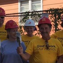 "A group of volunteers wearing hardhats and tee-shirts which say ""God's work, our hands""."