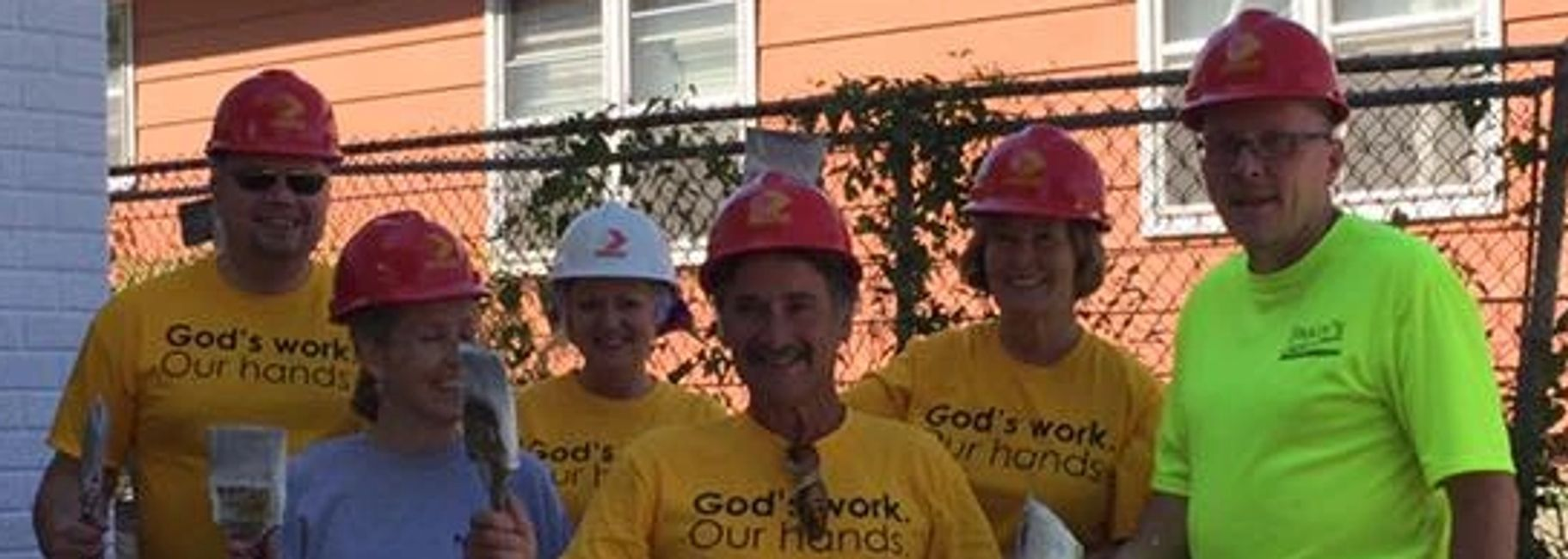 "Volunteers holding paintbrushes, wearing hardhats and tee-shirts which say ""God's work, our hands""."
