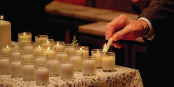Several rows of votive candles.  Several are lit and another is being lit.