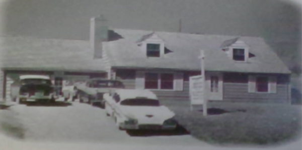 Old black and white photo of the parsonage house with late model cars in front