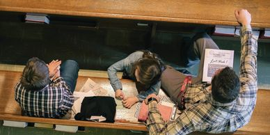 Overhead view of a father and 2 children in a pew.  One child is coloring in a coloring book.