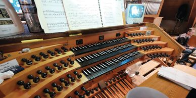 Rows of keys and stops at the organ keyboard.