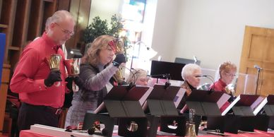 Bell choir members ringing bells during a performance.