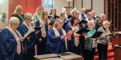 The adult choir singing in blue choir robes