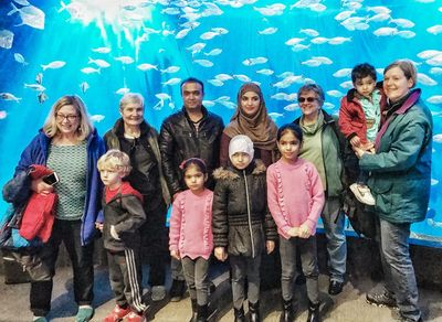 Group  of adults and children gathered in front of the aquarium at the zoo.