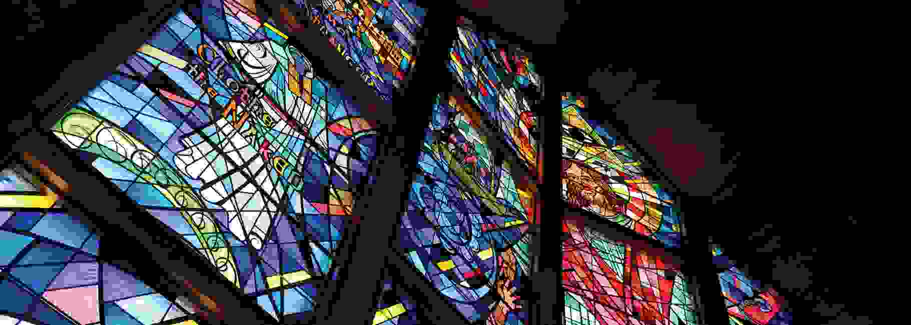 Dramatically-angled view of a large stained-glass window which depicts the Jesus walking on the sea.