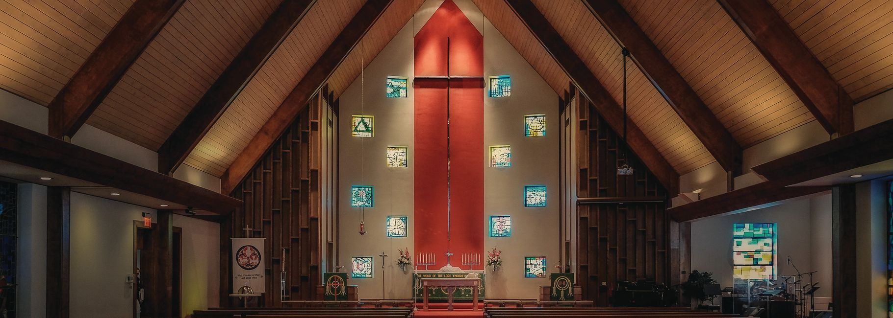 sanctuary with tall cross at the back of the altar on a red banner with wooden beamed cieling.