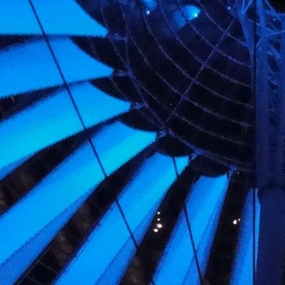 Large umbrella-like structure suspended from cables and lit in blue, seen from below