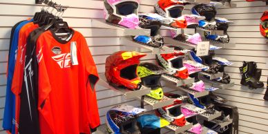 A collection of shirts and helmets at Highmark Rentals retail store.