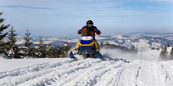 A man riding over a small hill on a snowmobile rental in West Yellowstone