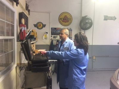 Everardo and Karolena Serratos, Houston Auto Repair Shop owners, performing a vehicle check out together.