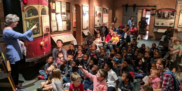 The museum during Children's Storytime. Around 40 children sitting on the floor and storyteller.