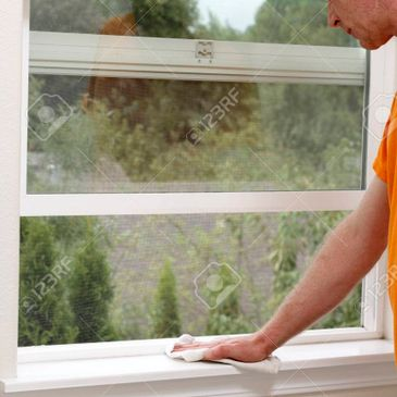 Person cleaning the interior window sill with a rag
