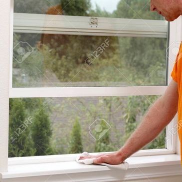 Person holding a rag to clean the interior window sill of a house