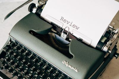 "image of Typewriter with the word ""review"" on the paper."