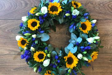 A funeral or memorial wreath designed into a oasis wreath ring. Sunflowers, freesia and eucalyptus.