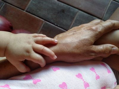 A child rests her hand on her ailing grandmother's arm.