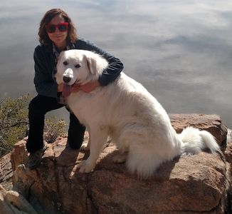 Marcy McDonald with red sunglasses hugging her therapy dog, a Great Pyrenees named Tigger in front of a lake.