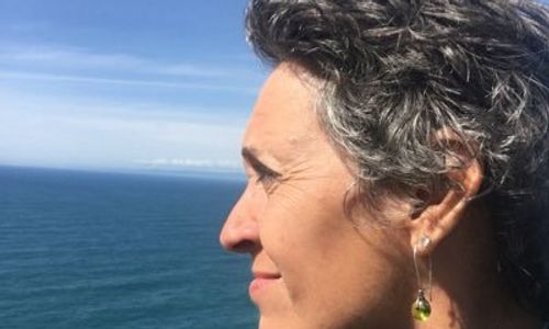 Sage Lewis, INELDA end of life doula, gazing at the ocean.