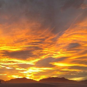A fiery sunset colored with orange and yellow setting over the mountains in CA.
