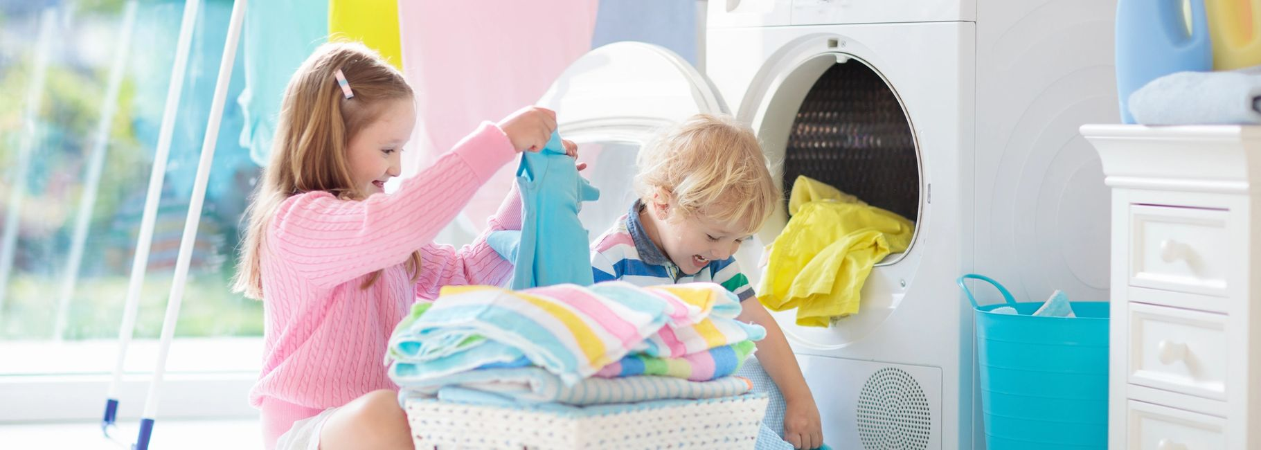 Kids Folding Laundry by Bosch Dryer and smiling