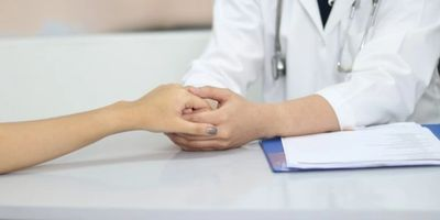 Doctor holding patients hand.