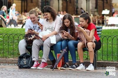 Girls with cellphones on a bench