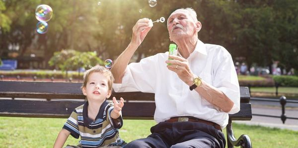 Elder blowing up soap bubbles to his grandson