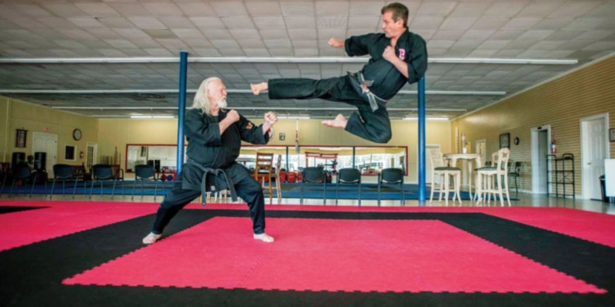 Ricky Smith, 61 years old, performs flying sidekick against his teacher, Jerry Piddington, 76 years
