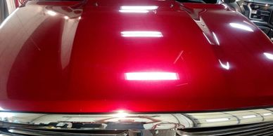 Shiny red hood on a pickup that has been treated with Flight Shield Sapphire V1 Paint Treatment
