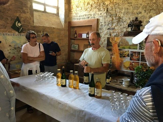 Bernard Lebrec offering cider to guests at his farmhouse distillery.