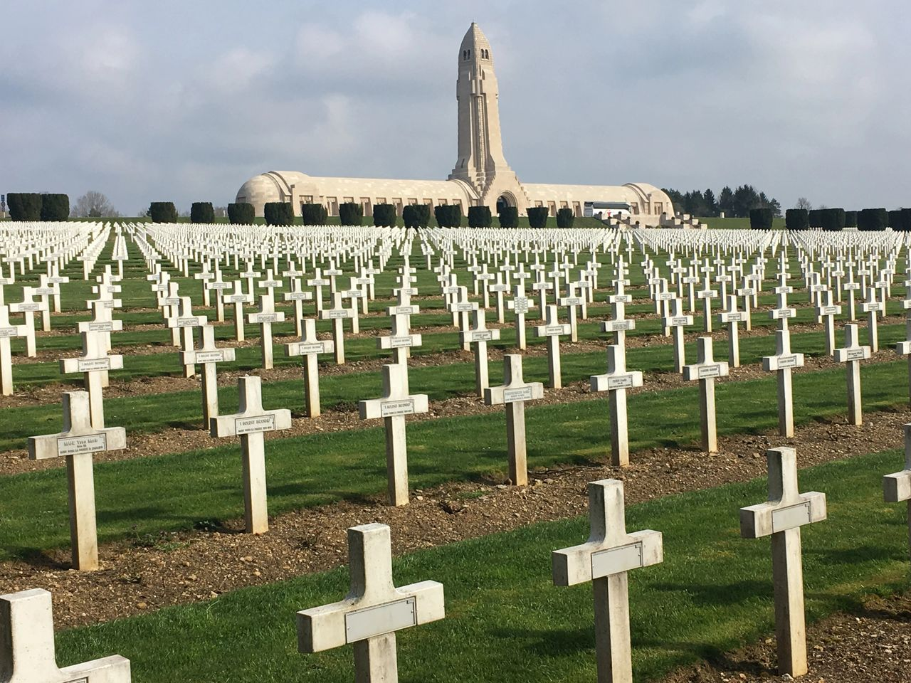 Sad cemetery in Verdun, with the stark and haunting Douaumont Ossuary in the background.