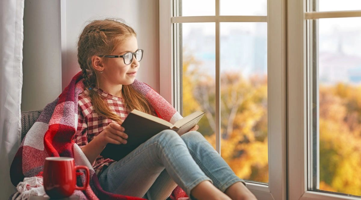 Girl sitting comfortable reading a book by the tinted window looking happy