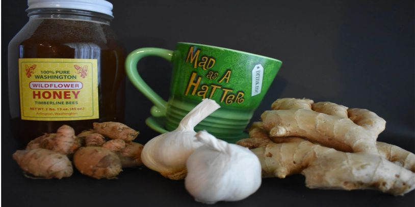 green  top hat cup says mad as a hatter, turmeric, ginger, jar of wildflower honey, garlic bulbs