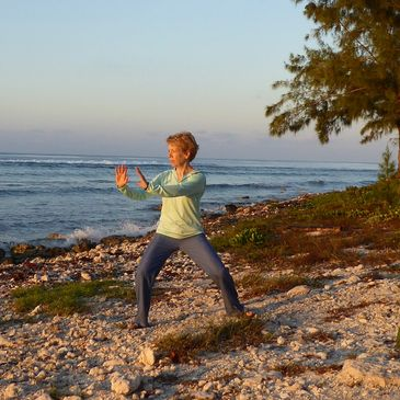 Christine Bhe, certified Tai Chi and Qigong instructor on a rocky beach with blue sky and trees