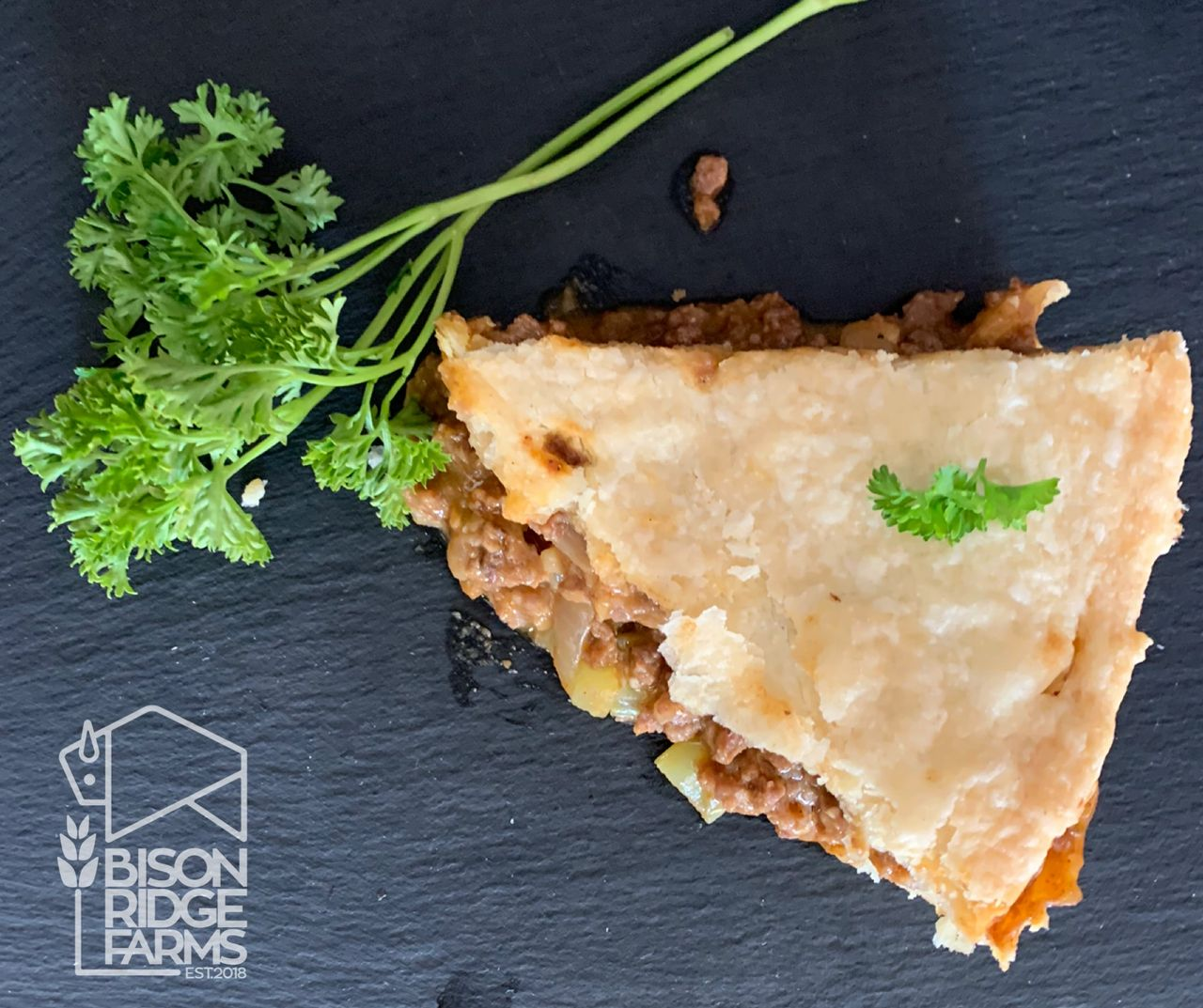 Slice of bison and cheddar pie garnished with parsley