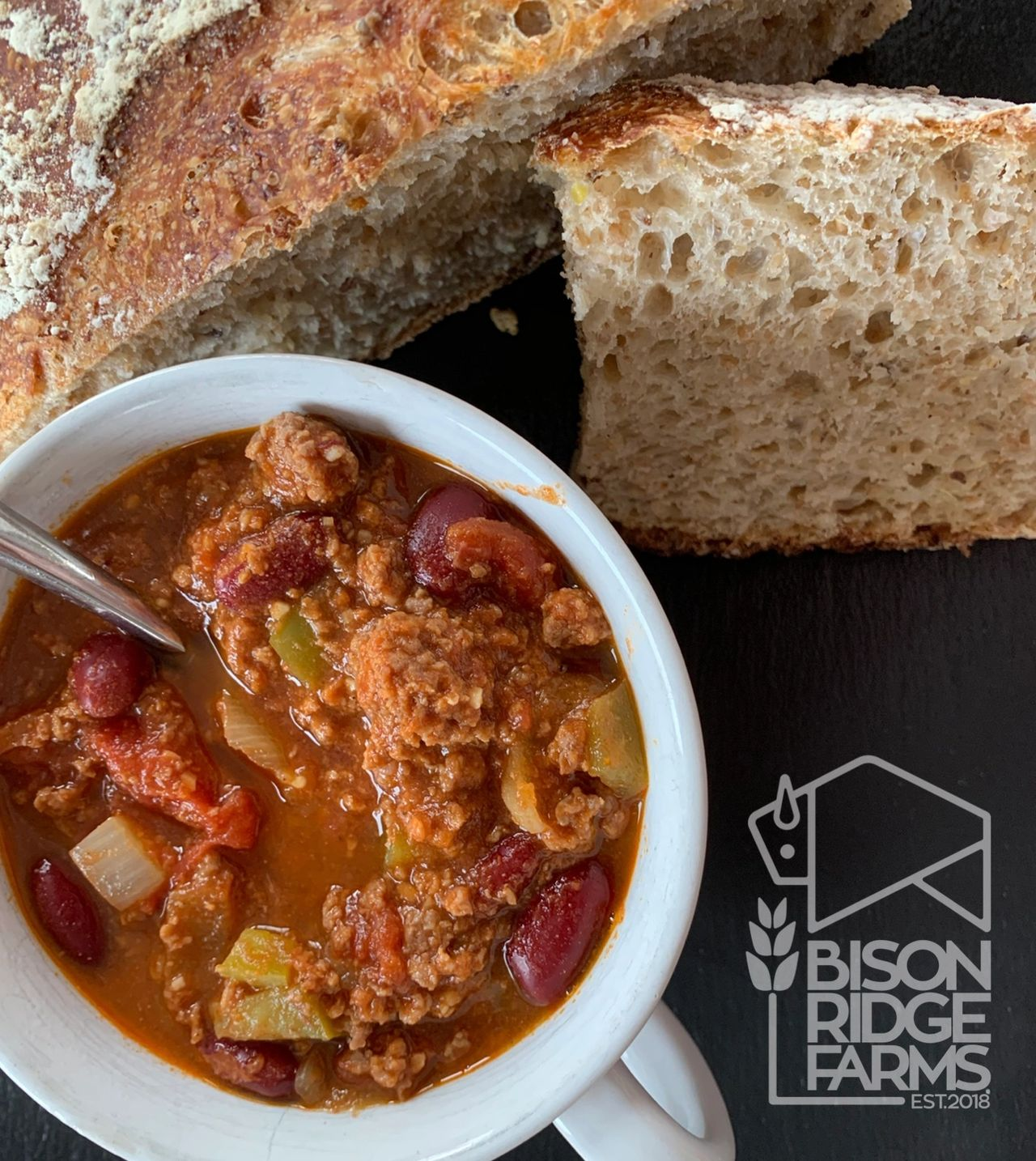 Bison chili in a large soup mug with a side of whole wheat bread