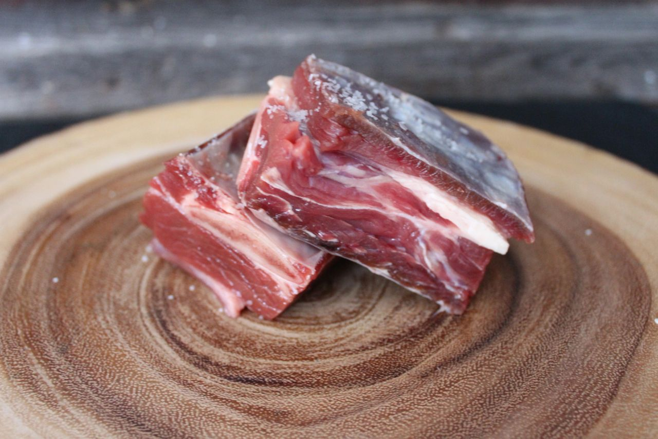 Raw bison short ribs on live edge cutting board