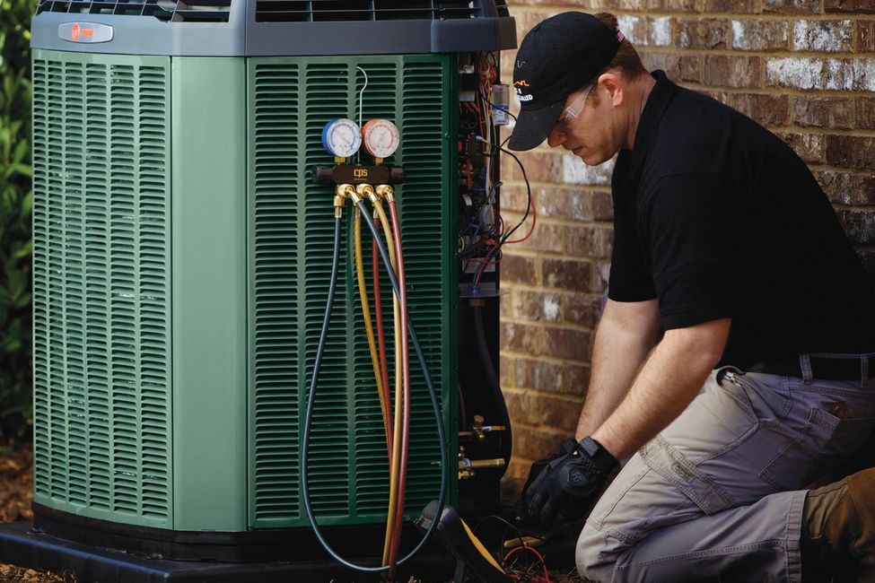 HVAC Technician kneeling next to an outdoor condenser testing the equipments refrigerant pressure