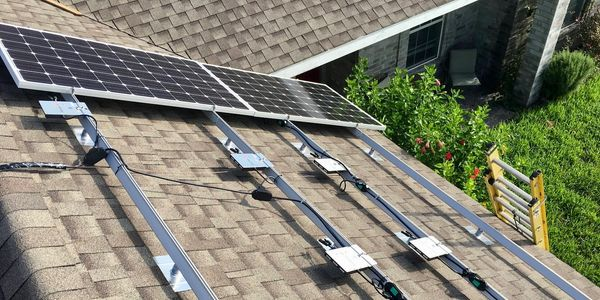 Solar installation on roof with racking and inverters showing