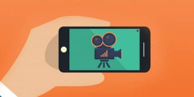 An animated image of a hand holding a mobile phone with an image of a film camera on it.