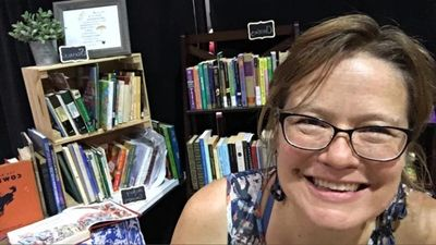 Heather Johnson  at the books stall of lovely living books at HERI, July 2019.